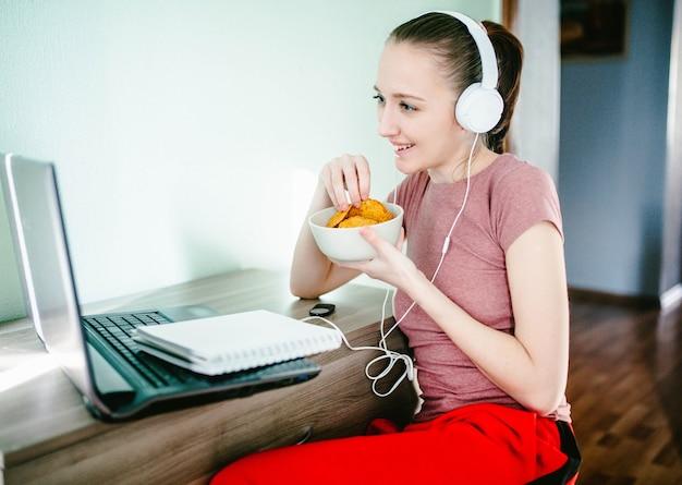 La chica joven se sienta en una computadora portátil en los auriculares, se ríe y come patatas fritas