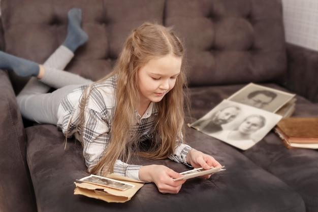 Chica joven se sienta en el sofá y mirando el viejo álbum de fotos familiar.