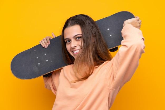 Chica joven skater sobre amarillo aislado