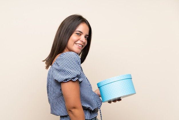 Chica joven sobre pared aislada con caja de regalo