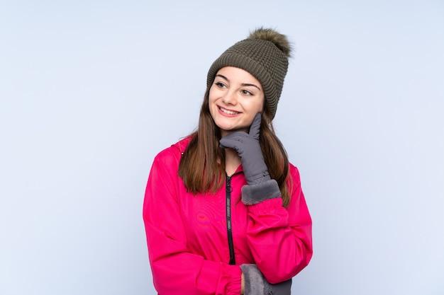 Chica joven con sombrero de invierno aislado en azul pensando una idea mientras mira hacia arriba