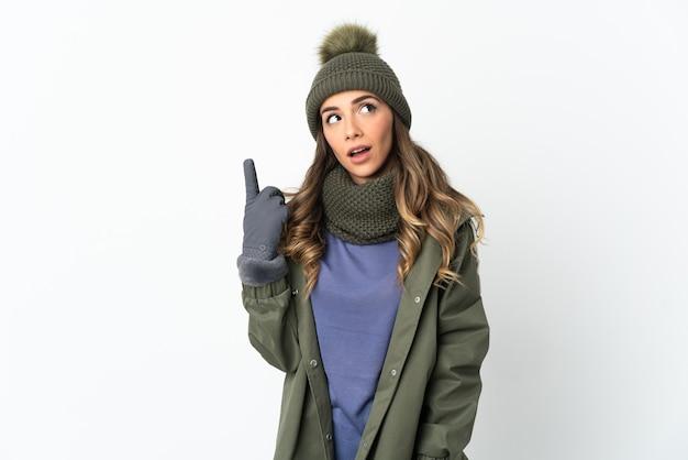 Chica joven con sombrero de invierno aislado en un espacio en blanco pensando en una idea apuntando con el dedo hacia arriba