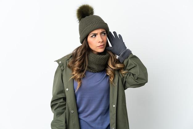 Chica joven con sombrero de invierno aislado en la pared blanca escuchando algo poniendo la mano en la oreja