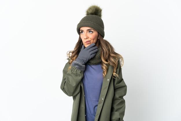 Chica joven con sombrero de invierno aislado en la pared blanca que tiene dudas