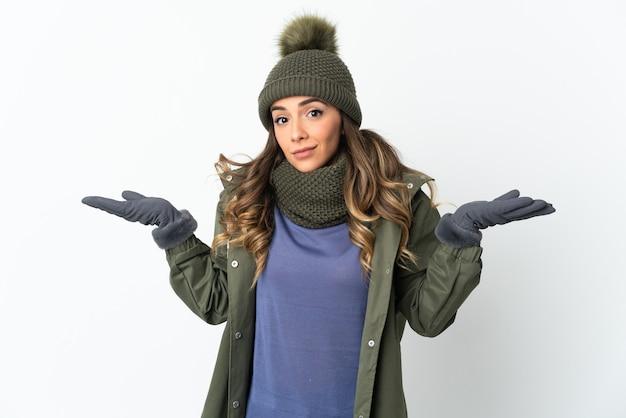 Chica joven con sombrero de invierno aislado sobre fondo blanco con dudas mientras levanta las manos
