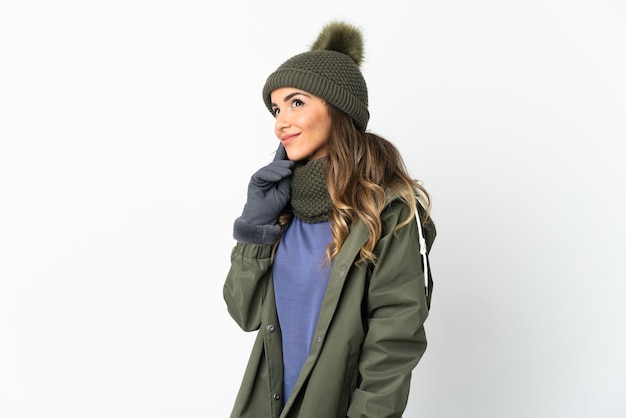 Chica joven con sombrero de invierno en blanco pensando en una idea mientras mira hacia arriba