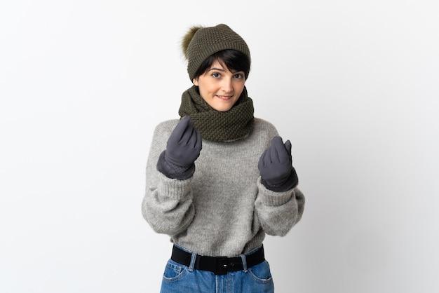 Chica joven con sombrero de invierno haciendo gesto de dinero