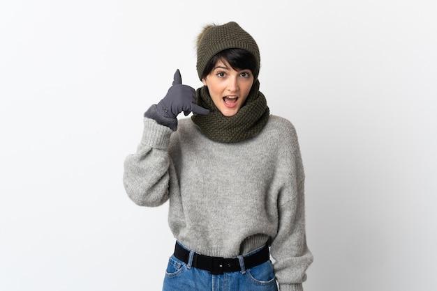 Chica joven con sombrero de invierno haciendo gesto de teléfono. llámame señal