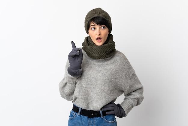 Chica joven con sombrero de invierno pensando en una idea apuntando con el dedo hacia arriba