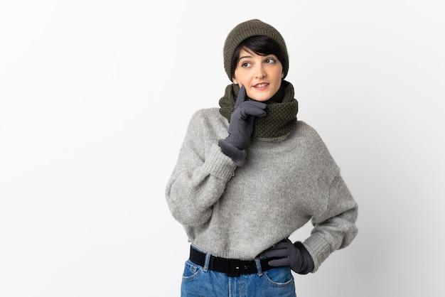 Chica joven con sombrero de invierno pensando en una idea mientras mira hacia arriba