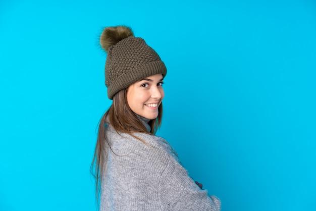 Chica joven con sombrero de invierno sobre pared aislada