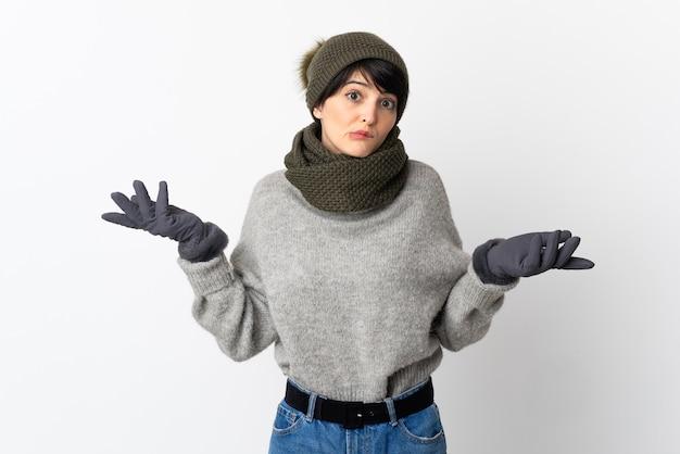 Chica joven con sombrero de invierno teniendo dudas mientras levanta las manos
