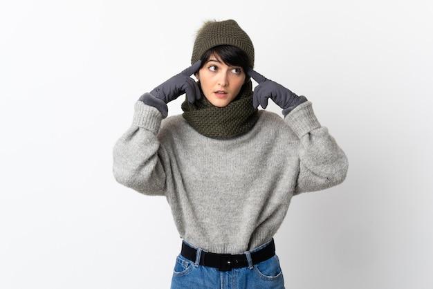 Chica joven con sombrero de invierno teniendo dudas y pensando