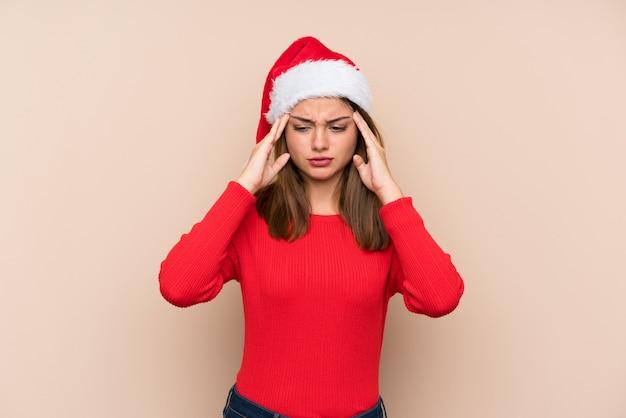 Chica joven con sombrero de navidad sobre pared aislada infeliz y frustrado con algo. expresión facial negativa