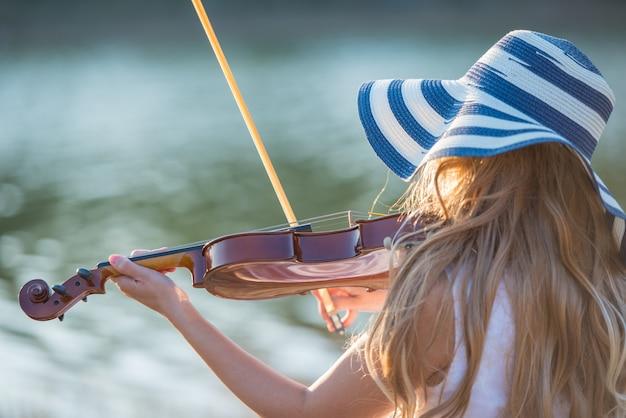 Chica joven con sombrero tocando el violín en el lago.