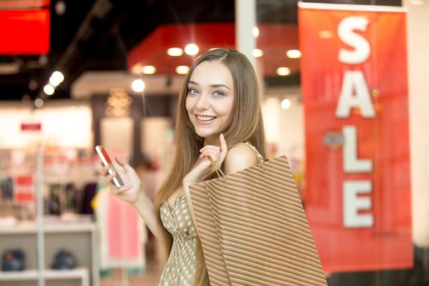 Chica joven sonriendo con una bolsa marrón
