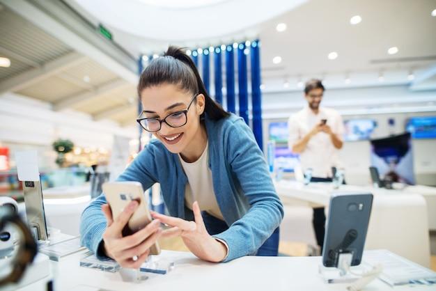 Chica joven sonriente linda que busca un nuevo teléfono en tienda electrónica. mirando el teléfono y sonriendo en la tienda brillante.
