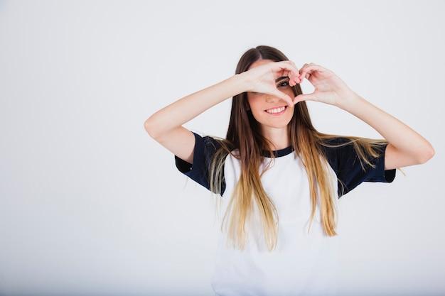 Chica joven sonriente y mirando a través de un corazón