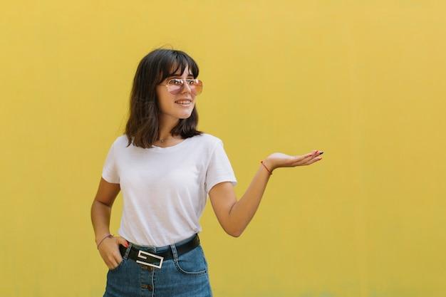 Chica joven sonriente en vidrios y apoyos mientras que está solo contra un fondo amarillo.