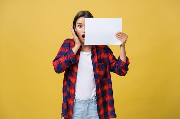 Chica joven sorprendida en camisa roja con el papel blanco del cartel en manos