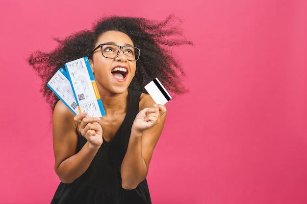 Chica joven sorprendida en casual en rosa en estudio. burlarse del espacio de la copia. con tarjeta de crédito, billetes de embarque.