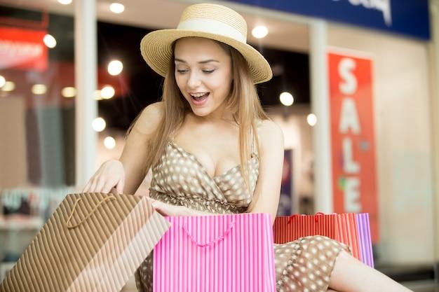 Chica joven sorprendida mirando bolsa de la compra