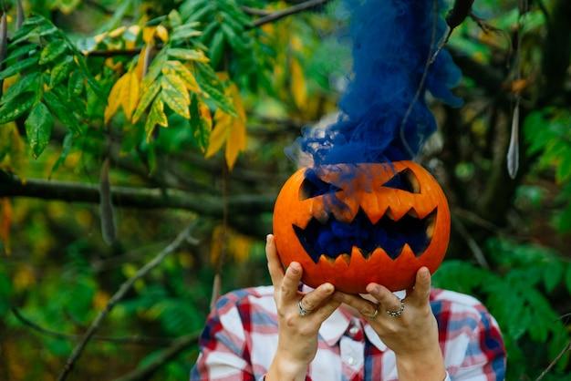 Chica joven sosteniendo calabazas ahumadas en el bosque. concepto sobre halloween, brujería y vacaciones