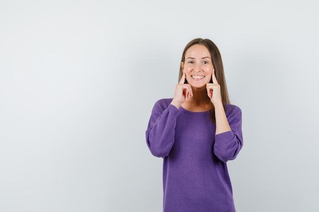 Chica joven sosteniendo los dedos en las mejillas en camisa violeta y mirando contento, vista frontal.
