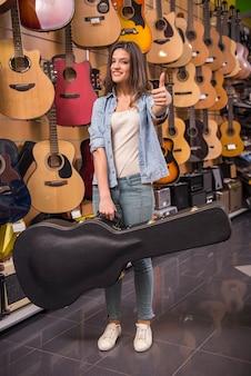La chica joven está sosteniendo una guitarra en un caso.