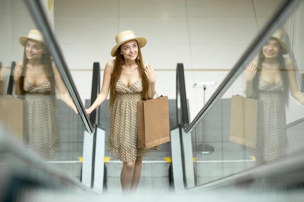Chica joven subiendo por unas escaleras mecánicas