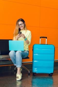 Chica joven en suéter amarillo y jeans está sentada en una silla sobre fondo naranja. ella tiene una computadora portátil azul en las rodillas y una maleta azul cerca. ella está escribiendo en el teléfono.