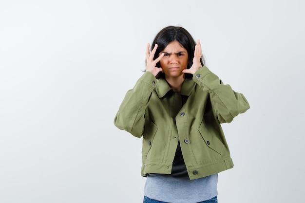 Chica joven en suéter gris, chaqueta caqui, pantalón de mezclilla cogidos de la mano cerca de la cabeza, haciendo muecas y mirando acosado, vista frontal.
