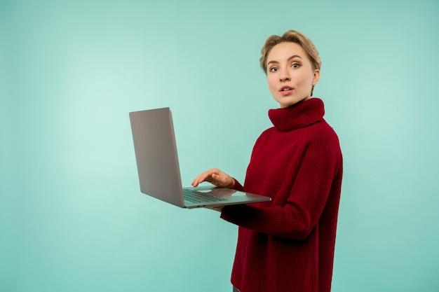Chica joven en un suéter rojo imprime algo en una computadora portátil en un espacio azul