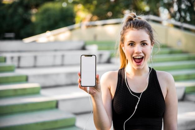 Chica joven sujetando un teléfono móvil