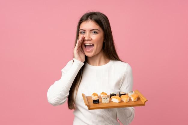Chica joven con sushi sobre gritos rosados aislados con la boca abierta