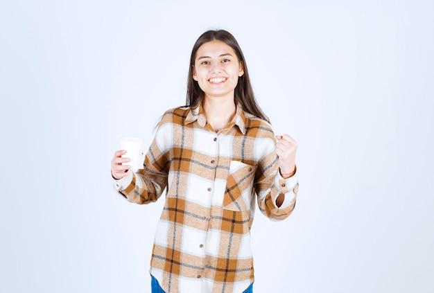 Chica joven con taza de té sintiéndose alegre en la pared blanca.