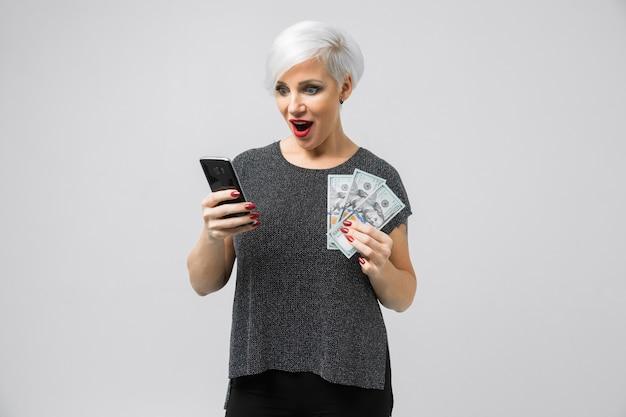 Chica joven con un teléfono y un abanico de dólares en sus manos se encuentra aislado una luz