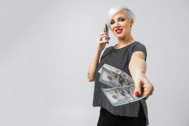 Chica joven con un teléfono y un abanico de dólares en sus manos se encuentra aislado