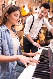 La chica joven está tocando el piano en una tienda de música.
