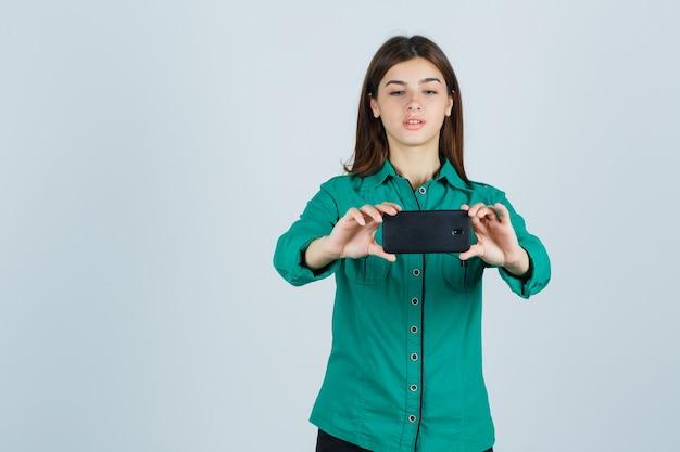 Chica joven tomando selfie en blusa verde, pantalón negro y mirando enfocado. vista frontal.