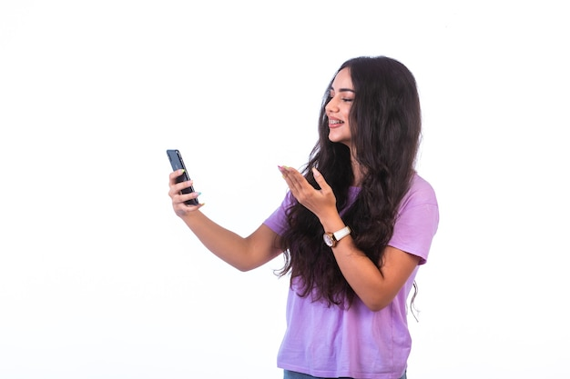 Chica joven tomando selfie o haciendo una videollamada y peinando su cabello.
