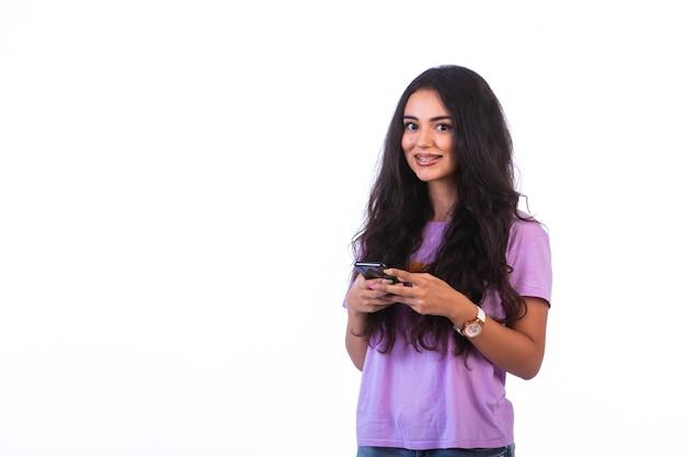 Chica joven tomando selfie o haciendo una videollamada sobre fondo blanco y sonriendo
