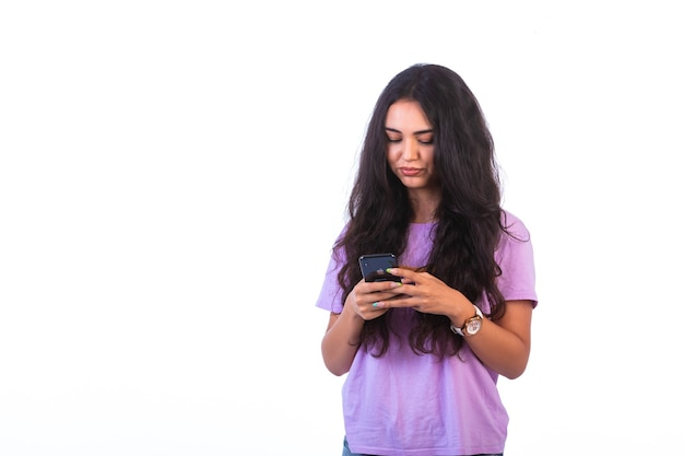 Chica joven tomando selfie o haciendo una videollamada sobre fondo blanco y se ve seria
