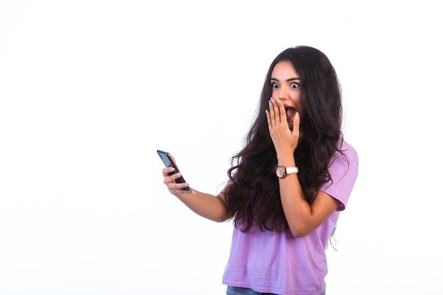 Chica joven tomando selfie o haciendo una videollamada y se sorprende sobre fondo blanco.