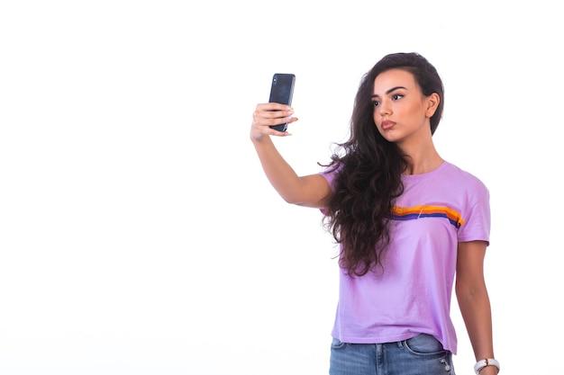 Chica joven tomando selfie o haciendo una videollamada, vista frontal