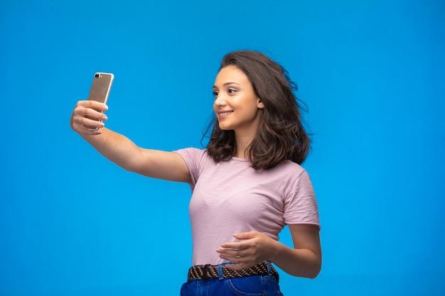 Chica joven tomando selfie con su teléfono inteligente y sonriendo.