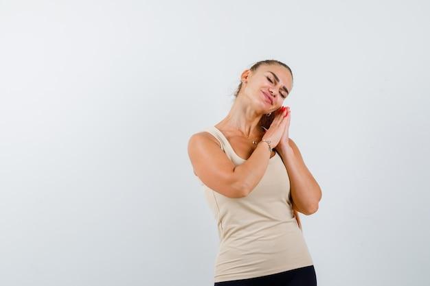 Chica joven en top beige, pantalón negro apoyando la mejilla en las palmas de las manos como almohada y mirando soñoliento, vista frontal.