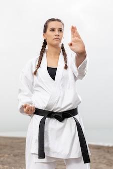 Chica joven en traje de karate al aire libre