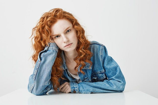 Chica joven triste disgustada con el pelo rizado jengibre sentado en la mesa.