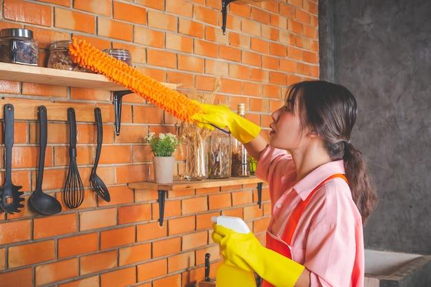 La chica joven está usando guantes amarillos mientras limpia la sala de cocina con plumero en su casa